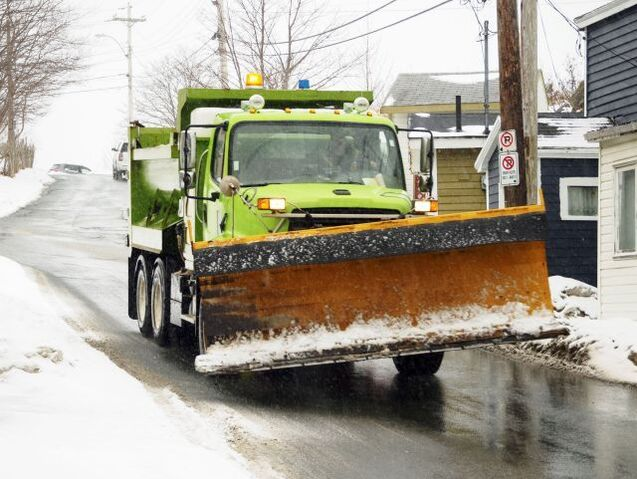 A green snow plow driving down a residential street in Syracuse