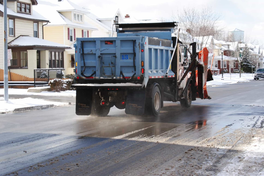 Snow plow dropping salt and sand to melt snow in residential Syracuse NY. About a foot of snow is on the ground around the truck